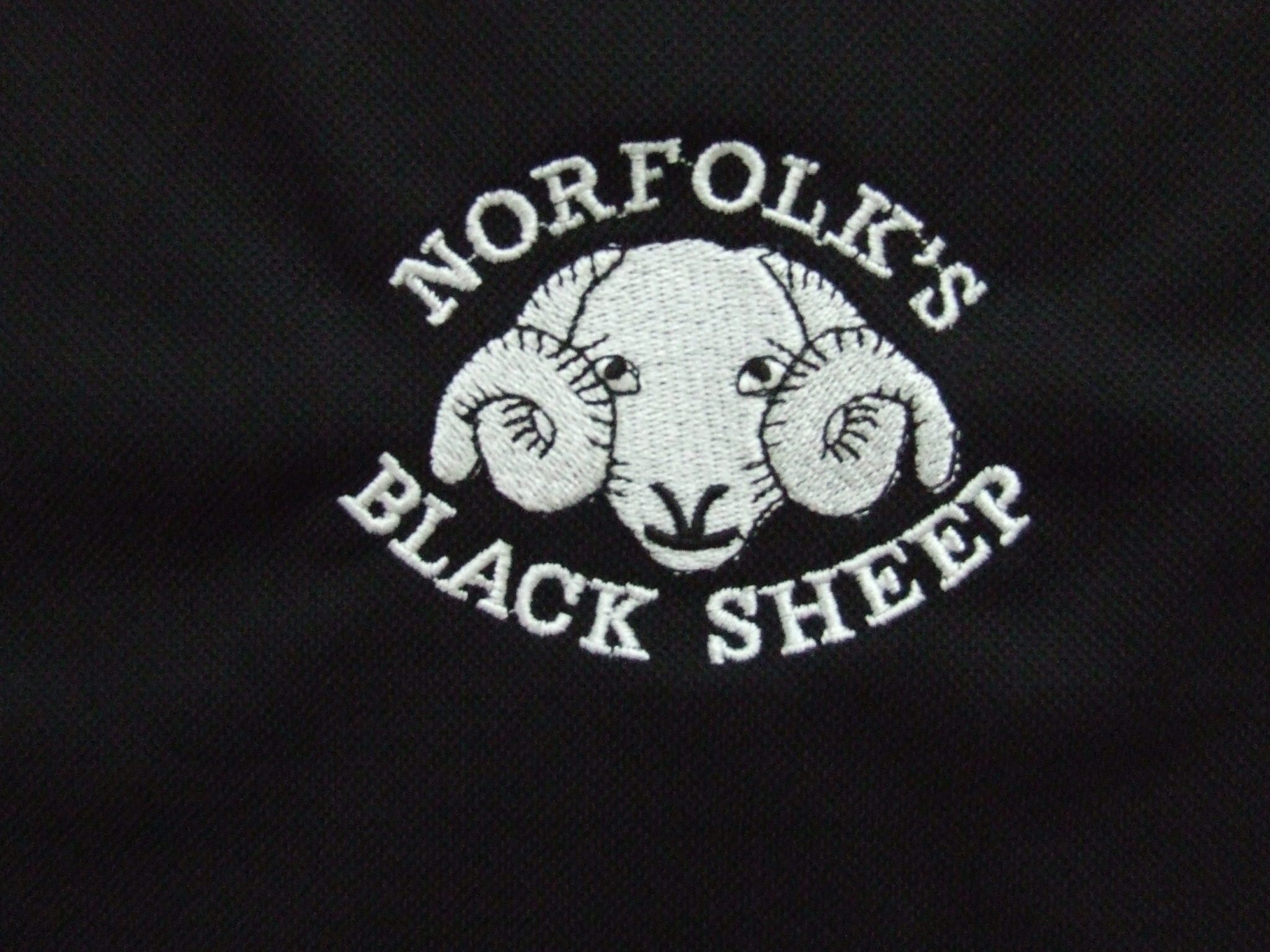 Detail of Black Sheep logo on polo shirt